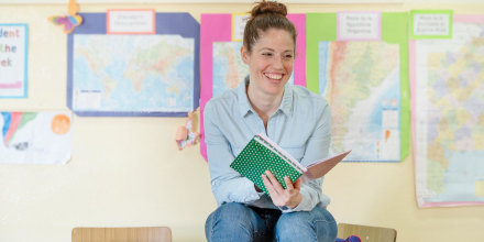 Teacher sitting on wooden desk in classroom, with a green book open in her hands