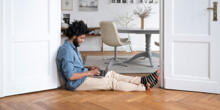 Man at home sitting on floor working with laptop in door frame. Here are the best work from home pants for men in 2021. Check out comfortable pants for men from brands like Everlane, Outdoor Voices, J.Crew and more.