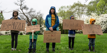 Image: A mother and her children hold anti-vaccination and anti-Covid19 mandate signs in protest on state capitol grounds on April 14, 2021 in Frankfort