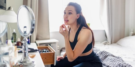 Woman looking in the mirror putting on makeup. Shop the best lighted makeup mirrors of 2021. These highly rated lighted makeup mirrors from RIKI and Fenair are available at Walmart, Amazon, Ulta and more.