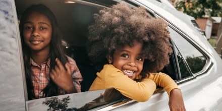Two little girls smiling while sticking their head out of the window