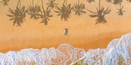 The guy lies on a sandy beach on a tropical island