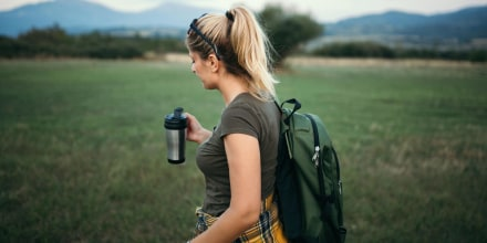 Woman is hiking in nature, with a backpack and holding a travel mug. The best travel mugs of 2021 include reusable cups, travel coffee mugs, ceramic travel mugs and stainless steel travel mugs from Ember, Contigo, YETI and more.