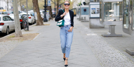 Woman walking down the street wearing stylish jeans
