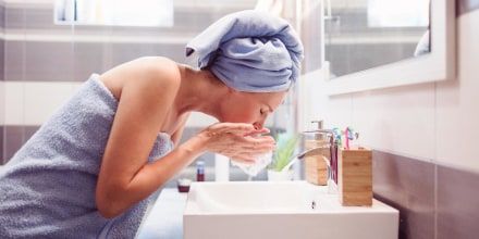 Woman washing her face in the bathroom sink, wearing a towel and a towel on her head