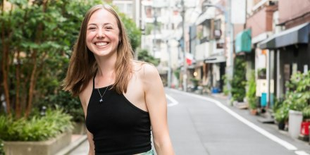 Woman smiling on the streets, wearing a black tank top and necklace