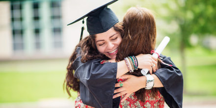 Woman in cap and gown hugging a family member, while holding her diploma