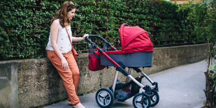 Image of a Mom pushing a baby in a red stroller, with a red diaper bag hanging on it