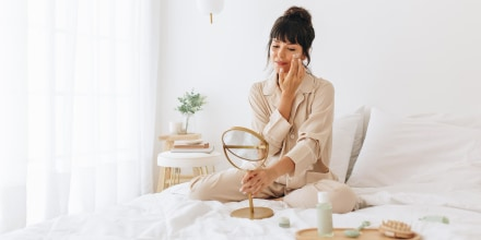 Woman doing self care applying beauty cosmetic, looking into mirror, while sitting in her bed