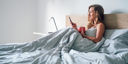 Woman sitting up in bed looking at smartphone, holding a red mug, wrapped in a grey duvet