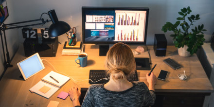 Woman working on computer desktop in her home office