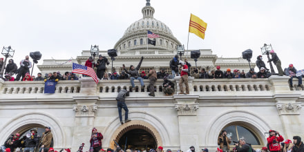 Image: Protesters climb over Capitol building where pro-Trump supporters riot and breached the Capitol,
