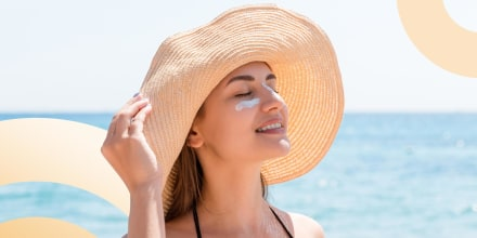 Woman protects her skin on face with sunblock at the beach