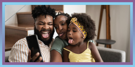 Parents with daughter taking a selfie on smartphone sticking out tongue at home
