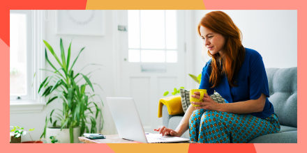 Woman using laptop from sofa and holding a coffee mug