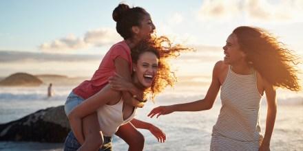 Young women piggybacking on sandy beach
