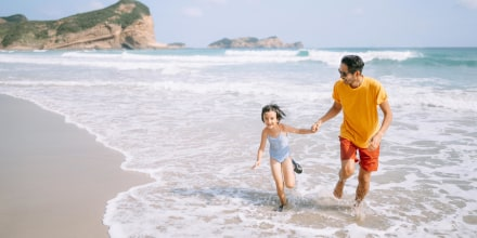 Father and daughter playing in waves on beach,
