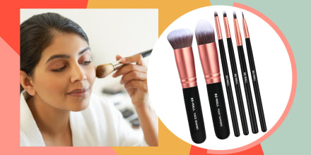 Woman applying make up with brush and a rose gold brush set