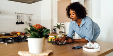 Woman using digital tablet and having a healthy breakfast in her kitchen. Find the best Wyze security and smart home products. Go with the classic Wyze camera, or shop other items like the Wyze Thermostat, Wyze Plug and more.