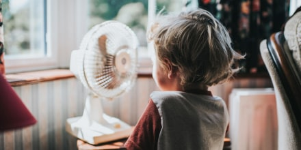 Little Boy looking at a fan in the window. Find the best window fan for cooling off during the hottest part of the year. Shop easy-to-install, easy-to-use and affordable fans to exhaust hot air and stay cool.