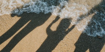 IMage: Shadows of a family holding hands on a beach as the ocean water rushes in.