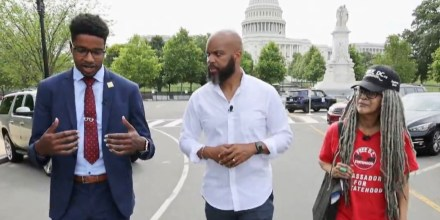 """Image: Trymaine Lee, center, speaks with Jamal Holtz from \""""51 for 51\"""" and Anise Jenkins from \""""Stand Up! for Democracy in DC\""""."""