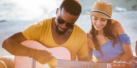Young hipster man playing the guitar at summer beach party