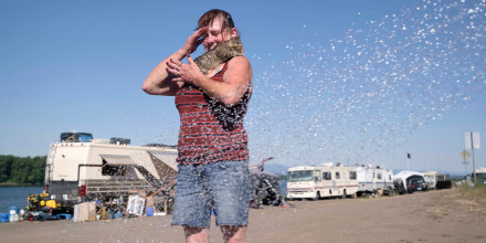 Image: Lisa Mirdahl cools off with her kitten Jazz after Mike Anderly stopped by with a water tank for people to use at a homeless camp along Northeast Marine Drive in Portland, Ore., on June 28, 2021, where temperatures reached an all time high of 116 de