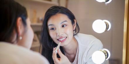 Young woman applying lip gloss through mirror