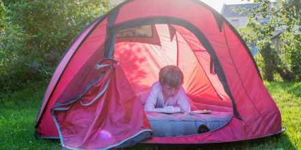 Boy reading in a red tent at evening twilight on an air mattress