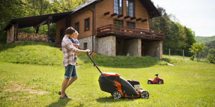 Father with his little son mowing the lawn