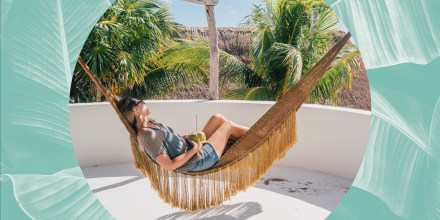 Woman relaxing in a Hammock, looking at the view, holding a coconut
