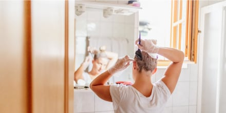 Woman dyeing hair in front of mirror