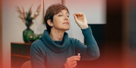 Senior woman using an nasal swab for covid 19 detection, self testing.