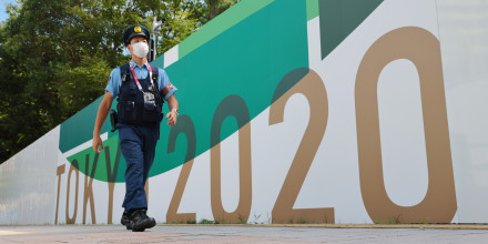 A police officer walks past a security wall during Tokyo Games on July 29, 2021.