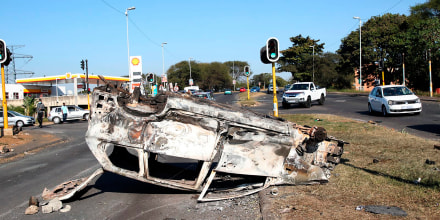 Image: A burnt out vehicle at an intersection in Phoenix, near Durban, South Africa, Fr