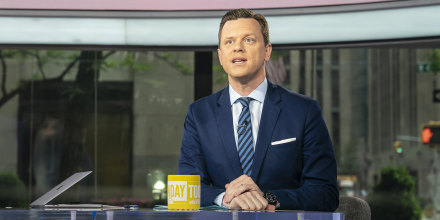 Willie Geist sitting at the desk with a yellow Sunday TODAY mug