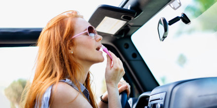 Woman doing make up in car, looking in her rearview mirror