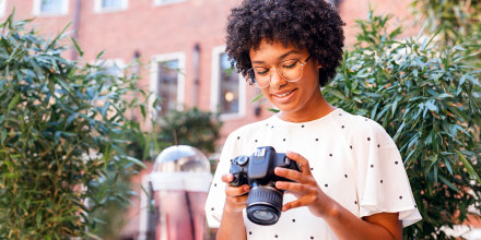 Woman sitting outside looking at a DSLR Camera