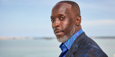 a close shot on Michael K. Williams who is looking at the camera over his shoulder in a blue button down shirt and black suit coat