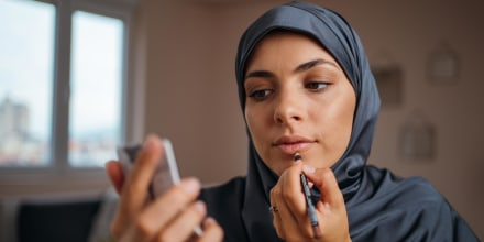 Young woman with hijab applying lip liner at home, while looking in handheld mirror