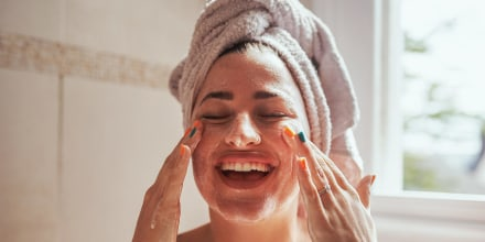 Woman smiling and scrubbing her face in the bathroom