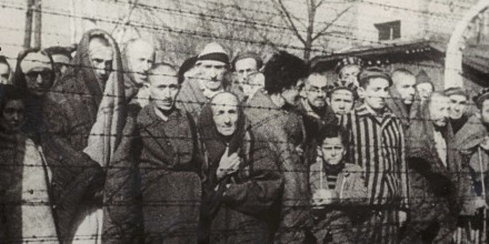 Image: FILE PHOTO: Holocaust survivors stand behind a barbed wire fence after the liberation of Nazi German death camp Auschwitz-Birkenau in 1945 in Nazi-occupied Poland, in this handout picture
