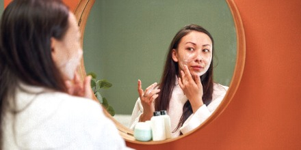 Woman applying moisture cream on her face, while looking in mirror