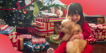 Little girl hugging a puppy she got for Christmas