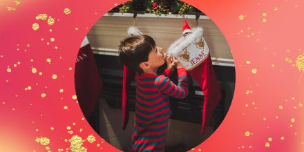 Curious boy looking at toy in sock hanging by fireplace during Christmas