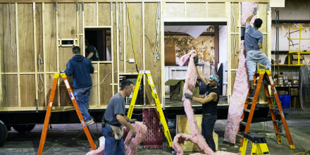 Image: Workers install insulation on the sides of a destination recreational vehicle at a manufacturing facility in Elkhart, Ind., on Oct. 8, 2020.