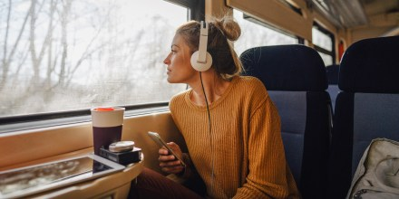 Photo of a young woman riding on a train, enjoying her trip while looking through the window and listening to some music on her mobile phone