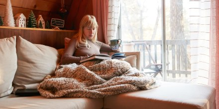 Woman reading book on sofa at home