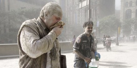 Carlos Nuñez, a paramedic, right, stands covered in dust after the collapse of the Twin Towers, in N.Y., on Sept. 11, 2001.